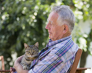 Image of older man holding his cat while sitting on bench