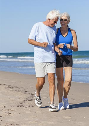 Image of older couple jogging on beach