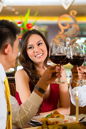 Image of well-to-do couple toasting with wine in restaurant