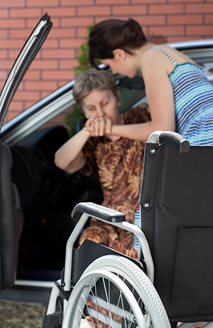 Image of young caregiver assisting woman from car.