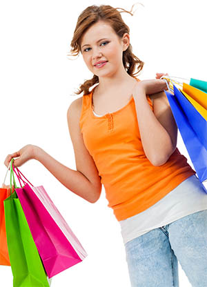 Image of young shopaholic with her hands full of brightly colored shopping bags